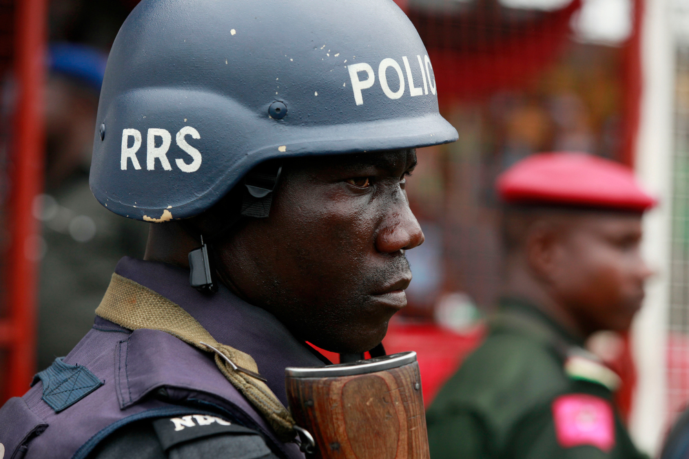 . A police officer stand guards during a demonstration calling on  government to rescue kidnapped school girls of a government secondary school Chibok, during workers day celebration in Lagos, Nigeria. Thursday, May, 1. 2014, Scores of girls and young women kidnapped from a school in Nigeria are being forced to marry their Islamic extremist abductors, a civic organization reported Wednesday. At the same time, the Boko Haram terrorist network is negotiating over the students\' fate and is demanding an unspecified ransom for their release, a Borno state community leader told The Associated Press. He said the Wednesday night message from the abductors also claimed that two of the girls have died from snake bites. The message was sent to a member of a presidential committee mandated last year to mediate a ceasefire with the Islamic extremists, said the civic leader, who spoke on condition of anonymity because he is not authorized to speak about the talks. (AP Photo/ Sunday Alamba)