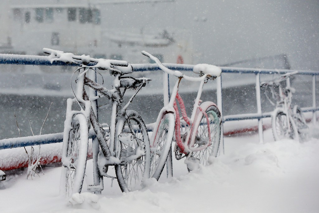 . Bicycles are chained to a railing are covered with snow at the Boston Harbor Shipyard and Marina in Boston, Tuesday, March 13, 2018.  The National Weather Service issued a blizzard warning for much of the coast of Maine, New Hampshire, and Massachusetts.  (AP Photo/Michael Dwyer)