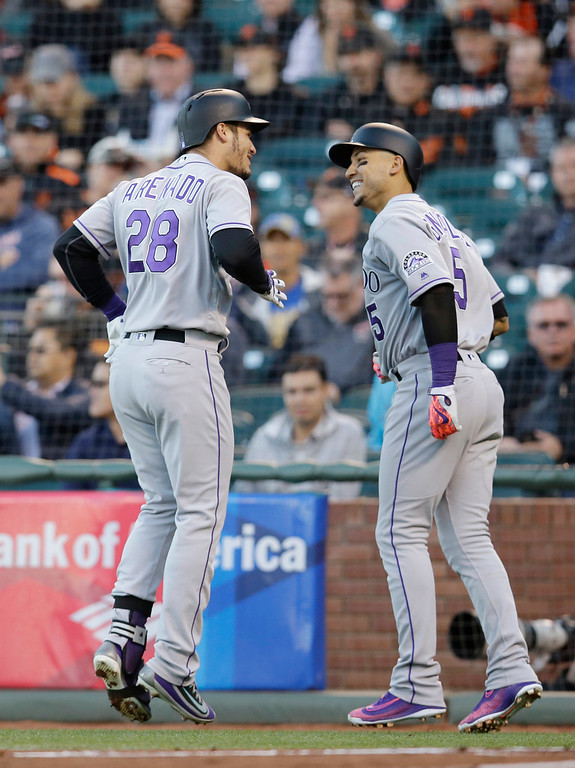 . Colorado Rockies\' Nolan Arenado (28) celebrates alongside teammate Carlos Gonzalez after Arenado\'s two-run home run against the San Francisco Giants during the first inning of a baseball game Thursday, May 5, 2016, in San Francisco. (AP Photo/Marcio Jose Sanchez)