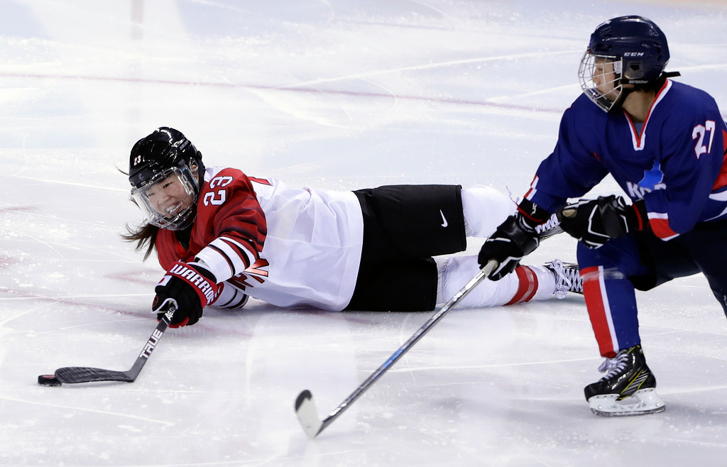 . Ami Nakamura (23), of Japan, tries to control the puck against North Korea\'s Jong Su Hyon (27), of the combined Koreas team, as she falls during the second period of the preliminary round of the women\'s hockey game at the 2018 Winter Olympics in Gangneung, South Korea, Wednesday, Feb. 14, 2018. (AP Photo/Frank Franklin II)