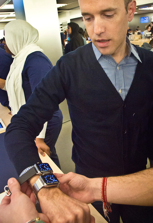 . Matt Kovich compares Apple\'s new watch, which customers could only pre-order online, Friday, April 10, 2015, in New York.  The first new gadget under CEO Tim Cook is selling in eight countries and Hong Kong, with shipments scheduled to start April 24.  (AP Photo/Bebeto Matthews)