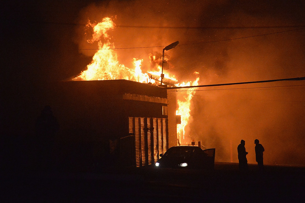. A local storage facility is set ablaze as demonstrators protest the death of 18-year-old unarmed black teenager Michael Brown, who was shot to death by a white police officer, in Ferguson on November 24, 2014. Protesters set buildings ablaze and looted stores in the US town of Ferguson on November 24 after a grand jury chose not to press charges against a white officer who shot dead a black teen. AFP PHOTO/Michael B. Thomas/AFP/Getty Images