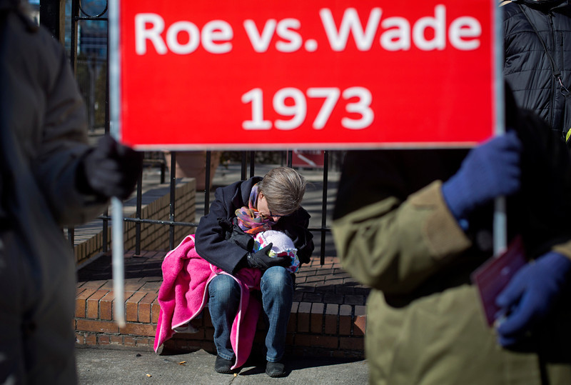 . Debbie Jung, of Sharpsburg, Ga., holds her one-year-old daughter Rose, beneath a sign protesting the 1973 Roe v. Wade Supreme Court decision legalizing abortion, during the March For Life anti-abortion rally outside the State Capitol, Wednesday, Jan. 22, 2014, in Atlanta. Hundreds of anti-abortion demonstrators gathered outside the Statehouse for the annual rally to protest the Supreme Court\'s landmark 1973 decision that declared a constitutional right to abortion. (AP Photo/David Goldman)