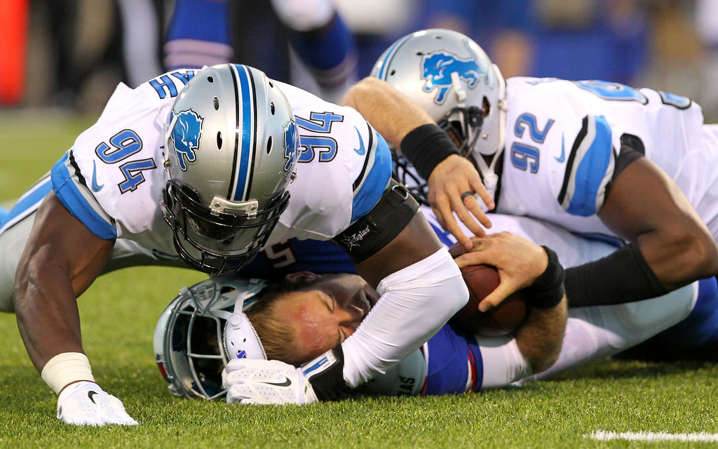 . Buffalo Bills quarterback Jordan Palmer, bottom, loses his helmet while being brought down by Detroit Lions defensive ends Devin Taylor (92) and Ezekiel Ansah (94) during the first half of a preseason NFL football game, Thursday, Aug. 28, 2014, in Orchard Park, N.Y. (AP Photo/Bill Wippert)