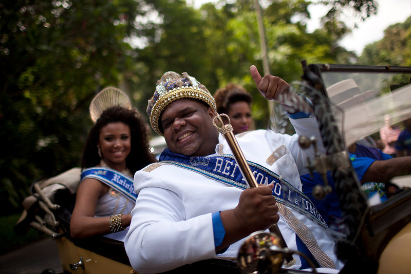 . The mythical jester figure who reigns over Carnival, this year\'s King Momo; the crowned and costumed Milton Rodrigues Junior, arrives at the official ceremony kicking off the five-day bash, in Rio de Janeiro, Brazil, Friday, Feb. 8, 2013. (AP Photo/Felipe Dana)