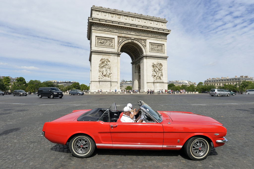 ". A person drives a convertible Ford Mustang car in front of the Arch of Triumph in Paris, on July 28, 2013, during a vintage cars parade as part of the sixth summer edition of the ""Traversee de Paris Estivale\"" (\""Summer Paris Crossing\""), the largest gathering of classic vehicles in the French capital streets. MIGUEL MEDINA/AFP/Getty Images"