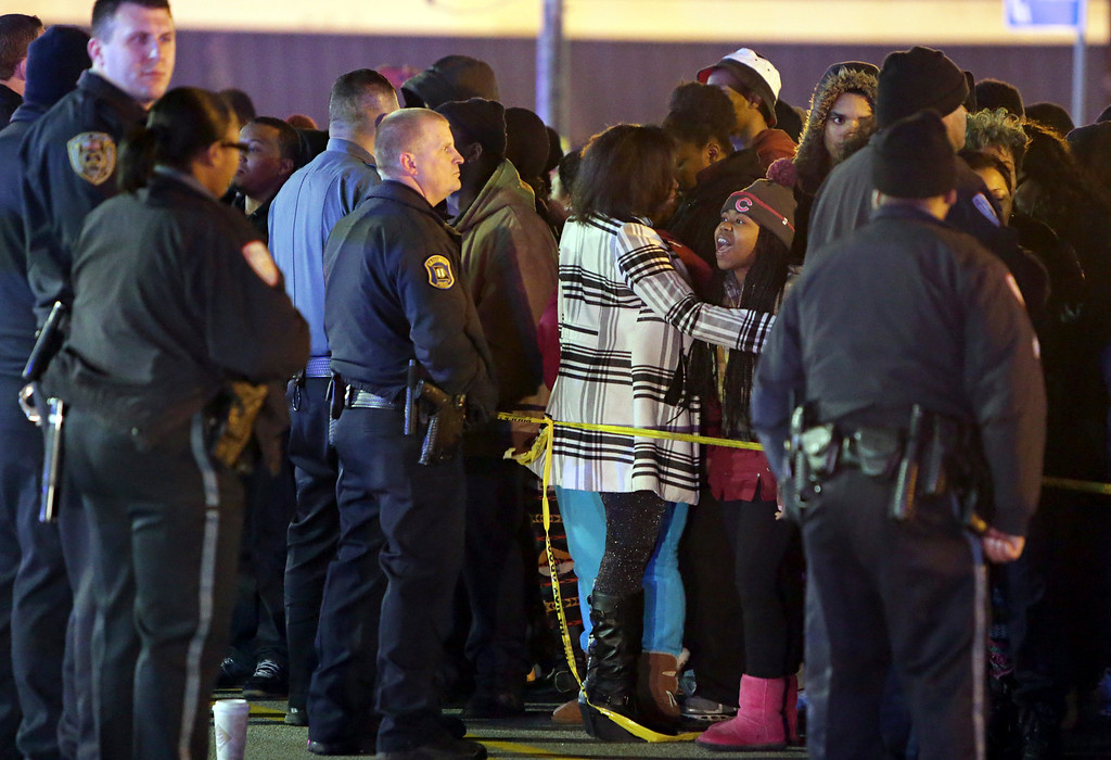 . Police hold back a crowd at the perimeter of a scene on Wednesday, Dec. 24, 2014, following a shooting Tuesday at a gas station in Berkeley, Mo. St. Louis County police say a man who pulled a gun and pointed it at an officer has been killed. (AP Photo/St. Louis Post-Dispatch, David Carson)