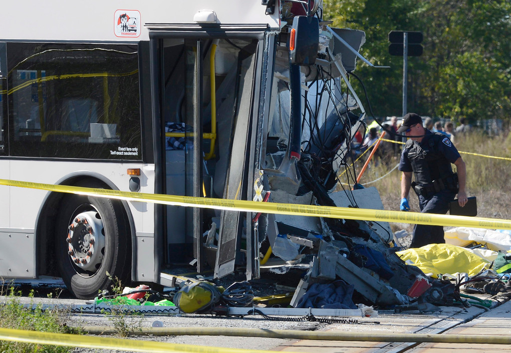 . A rescue worker looks over the crash scene following a Via Rail train and city bus collision in Ottawa\'s west end Wednesday, Sept. 18, 2013.  Multiple people were killed when a passenger train collided with a city bus at a crossing at the peak of morning rush hour, police said Wednesday.  Rescue crews swarmed over the wreckage. The injured from the bus who would walk were taken to a second bus nearby to be treated by paramedics. The train tracks in the area cross both a major city street and a transit line reserved for buses only.  (AP Photo/The Canadian Press, Adrian Wyld)