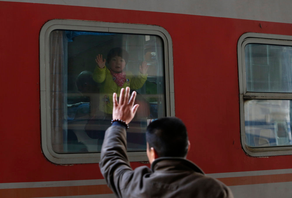 Description of . A child waves to his father from a train as it leaves from Hangzhou railway station in Hangzhou, Zhejiang province January 27, 2013. The 2013 Spring Festival travel peak period began on Saturday and will last till March 6. According to the Ministry of Transport, over 3.1 billion people are expected to travel via road or waterways during this period, a year-on-year increase of 4 percent, local media reported. REUTERS/William Hong
