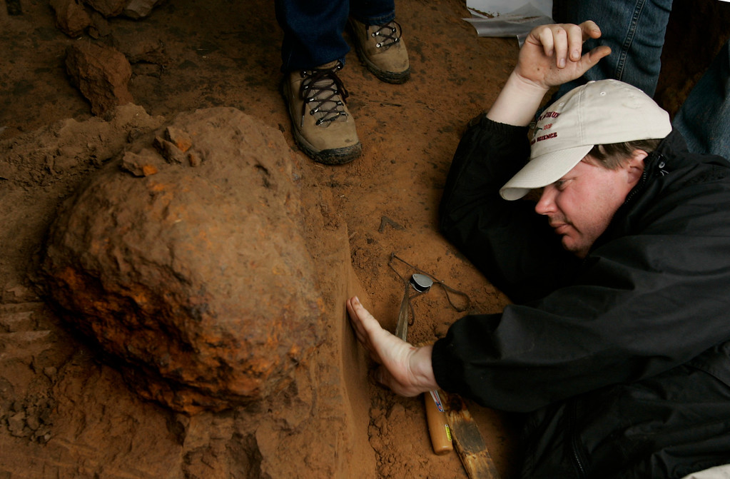 . Houston Museum of Natural Science worker David Temple examines the soil beneath a meteor as workers from the museum dig up the find in a field near Greensburg, Kan., Monday, Oct. 16, 2006. (AP Photo/Charlie Riedel)