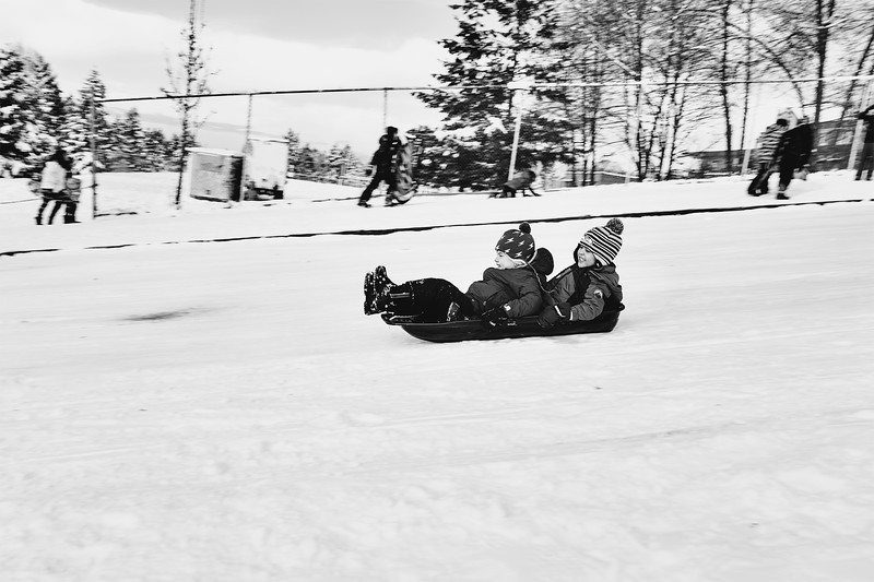 Two young boys enjoy a sled ride down Spokane Street, next to Madison middle school.