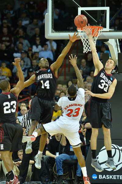 March 20, 2014: Harvard Crimson forward Steve Moundou-Missi (14) and Harvard Crimson forward Evan Cummins (33) contest a shot from Cincinnati Bearcats guard Sean Kilpatrick (23) during a second round game of the NCAA Division I Men's Basketball Championship between the 5-seed Cincinnati Bearcats and the 12-seed Harvard Crimson at Spokane Arena in Spokane, Wash. Harvard defeated Cincinnati 61-57.