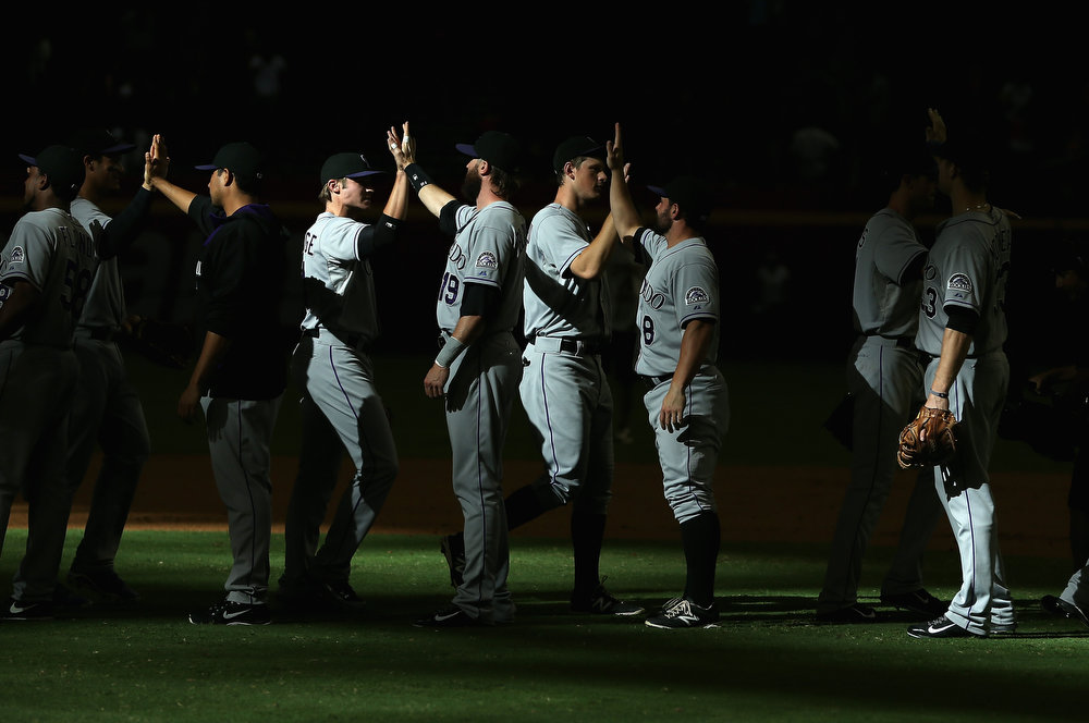 . The Colorado Rockies celebrate after defeating the Arizona Diamondbacks 5-3 in the tenth inning of the MLB game at Chase Field on August 10, 2014 in Phoenix, Arizona.  (Photo by Christian Petersen/Getty Images)