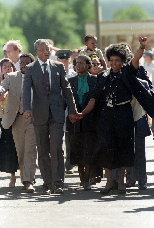 . Nelson Mandela is led by his wife, Winnie Mandela, who gives a black power salute, after his release from Victor Verster prison in Cape Town, South Africa, Sunday, Feb. 11, 1990.  The leader of the African National Congress served over 27 years in jail.  (AP Photo/Greg English)
