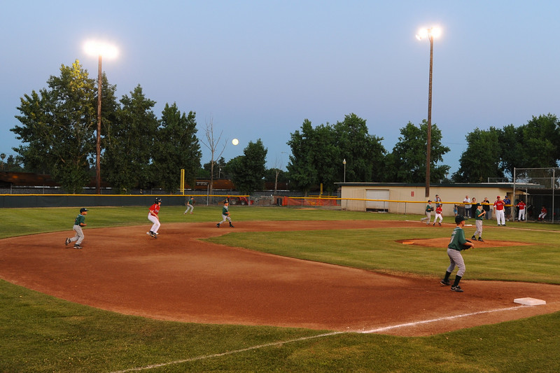 Full moon rising as the train passes by the Tulare Cal Ripken Baseball diamond.  Tulare has a first class operation!