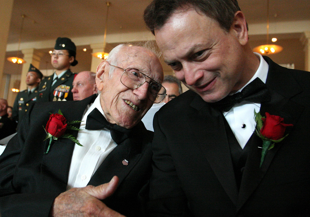 ". In this May 10, 2008 file photo provided by the National Ethnic Coalition, 91-year-old World War II veteran and member of the U.S. Olympic team during the 1936 Berlin Olympics Louis Zamperini, left, shares a moment with actor and founder of ""Operation Iraqi Children\"" Gary Sinise before the start of the 2008 Ellis Island Medals of Honor ceremony on Ellis Island. Zamperini, a U.S. Olympic distance runner and World War II veteran who survived 47 days on a raft in the Pacific after his bomber crashed, then endured two years in Japanese prison camps, died Wednesday, July 2, 2014, according to Universal Pictures studio spokesman Michael Moses. He was 97.  (AP Photo/National Ethnic Coalition, Tina Fineberg, File)"