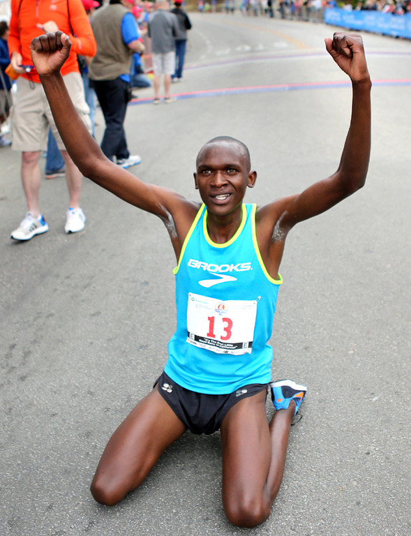 . An exhausted Nelson Oyugi celebrates at the finish line of the 2013 Wharf to Wharf race in Capitola on Sunday after finishing first place. (Kevin Johnson/Sentinel)