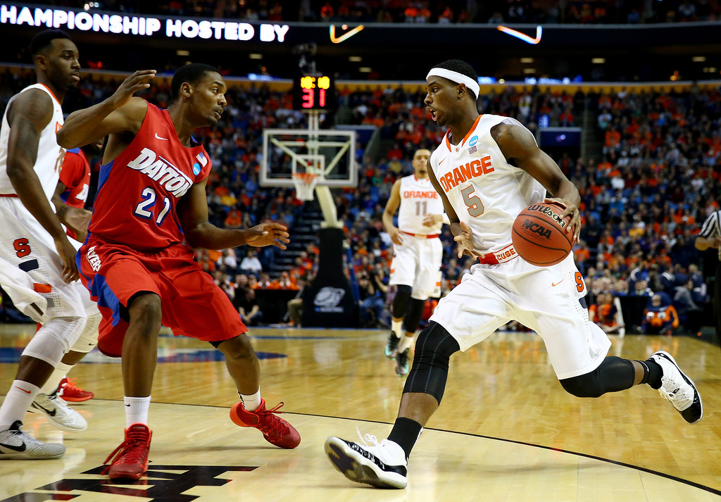 . BUFFALO, NY - MARCH 22: C.J. Fair #5 of the Syracuse Orange drives to the basket as Dyshawn Pierre #21 of the Dayton Flyers defends during the third round of the 2014 NCAA Men\'s Basketball Tournament at the First Niagara Center on March 22, 2014 in Buffalo, New York.  (Photo by Elsa/Getty Images)
