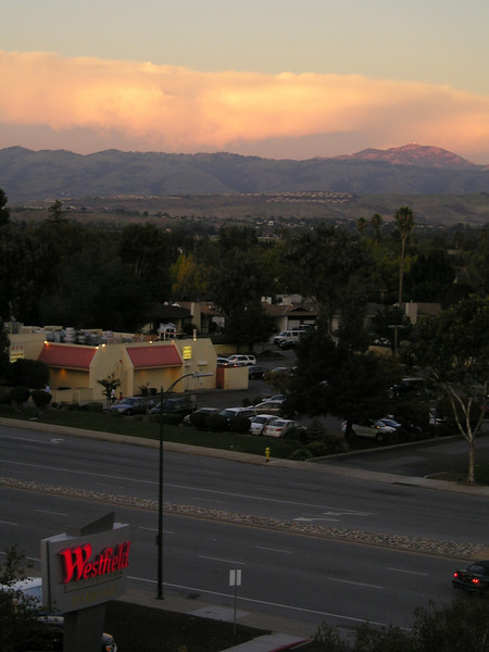 """Looking east across the nearby shopping area towards Mount Hamilton (Lick Observatory just visible on top). In this photo, we can see that we are in """"Westfield""""'s Shoppingtown Oakridge. Lots of red lit-up signs around here. (From top level of Oakridge Shopping Center parking garage.)"""
