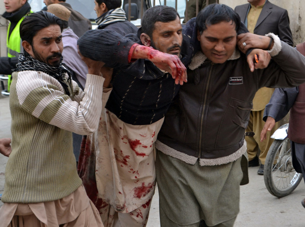 . Pakistani men help an injured blast victim to a hospital after a bomb explosion in Quetta on January 10, 2013. A bomb attack killed 11 people and wounded dozens more in a crowded part of Pakistan\'s southwestern city of Quetta, police said. AFP PHOTO/Banaras KHAN/AFP/Getty Images