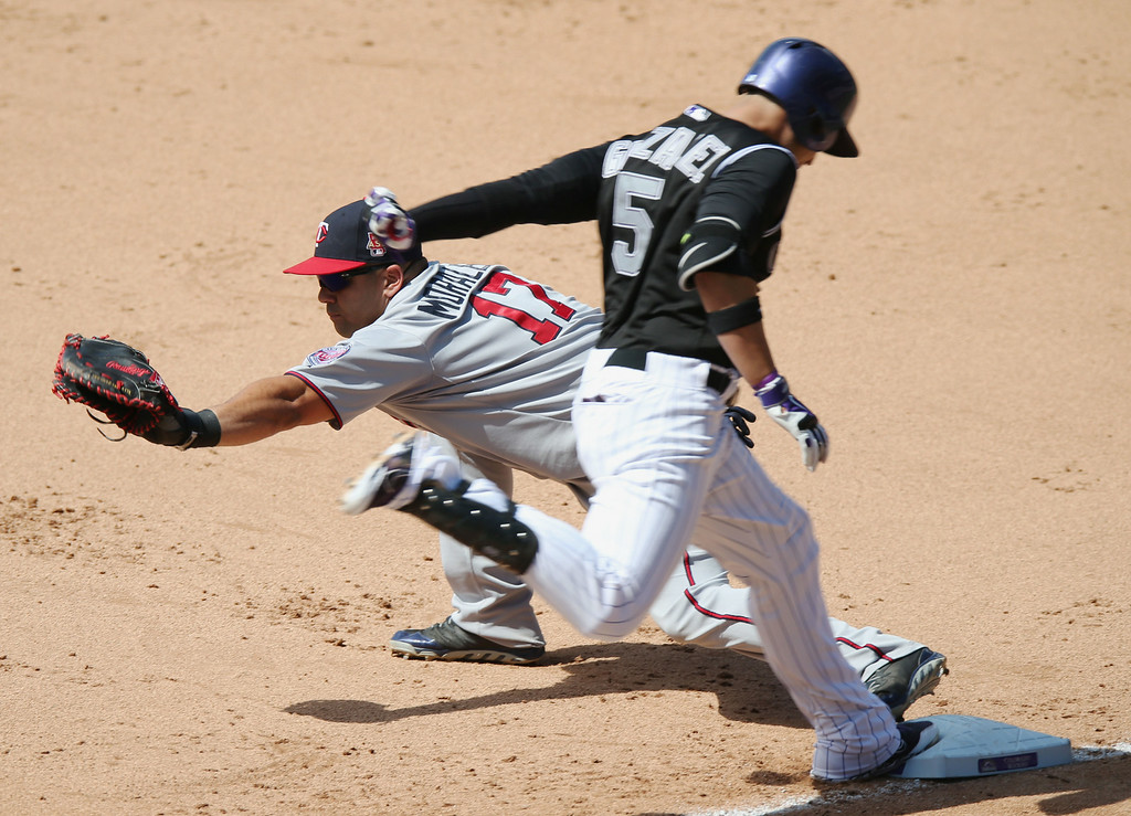 . Minnesota Twins first baseman Kendrys Morales, back, fields a throw to put out Colorado Rockies Carlos Gonzalez at first base after a dropped third strike in the fourth inning. (AP Photo/David Zalubowski)