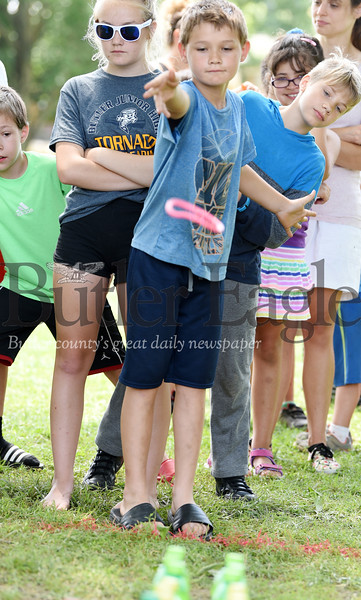 Harold Aughton/Butler Eagle: Zack Zeigler, 10, of Butler, takes a turn at tossing a ring on the pop bottles at the carnavil held at Rotary Park, Friday, June 28.
