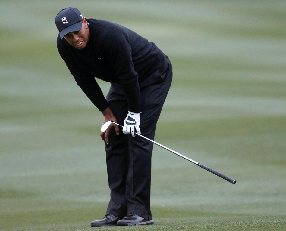 . Tiger Woods of the U.S. reacts after hitting his second shot on the 15th hole against Charlies Howell III of the U.S. during the weather-delayed first round of the WGC-Accenture Match Play Championship golf tournament in Marana, Arizona February 21, 2013. REUTERS/Matt Sullivan