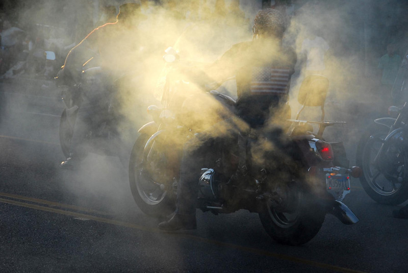 6/16/07 – The first motorcycle has his front brake locked up while his back tire is burning rubber creating this thick smoke as the late evening sun filters through the trees creating an interesting image.