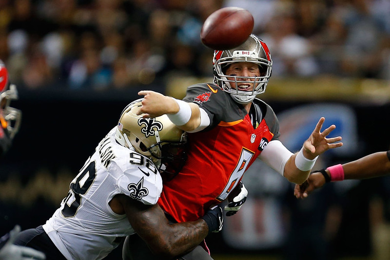 . Mike Glennon #8 of the Tampa Bay Buccaneers is pressured by Parys Haralson #98 of the New Orleans Saints during the fourth quarter of a game at the Mercedes-Benz Superdome on October 5, 2014 in New Orleans, Louisiana.  (Photo by Wesley Hitt/Getty Images)
