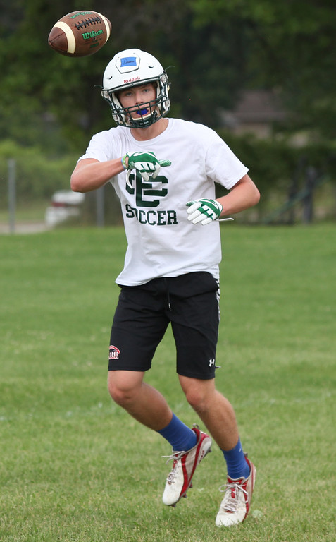 . Randy Meyers - The Morning Journal<br> Nate Damron flips the ball to a teammate during Elyria Catholic\'s first football practice on July 30.