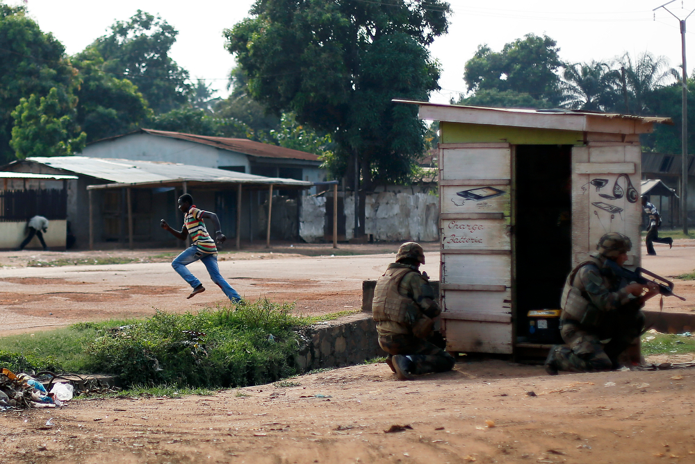 . Men run across the Avenue de France while French forces take cover  as heavy gunfire erupts in the Miskin district of Bangui, Central African Republic, Monday Feb. 3, 2014. In what a French soldier on the scene describes as the heaviest exchange of fire he\'d seen since early December 2013, Muslim militias engaged Burundi troops who returned fire. A third source of firing remained unidentified. Fighting between Muslim Seleka militias and Christian anti-Balaka factions continues as French and African Union forces struggle to contain the bloodshed. (AP Photo/Jerome Delay)