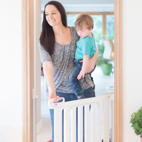 Fred_Stairgates_Screw_Fit_Wooden_Gate_Lifestyle_white_mum_boy_in_arm_opening.jpg