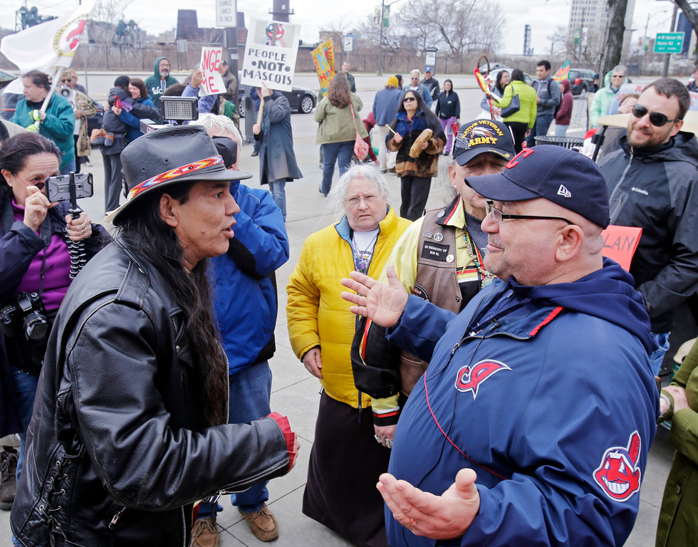 . Philip Yenyo, left, executive director of the American Indians Movement for Ohio, talks with a Cleveland Indians fan before a baseball game against the Detroit Tigers Friday, April 10, 2015, in Cleveland. A small group demonstrated against the Indians\' Chief Wahoo mascot outside the ballpark. (AP Photo/Mark Duncan)