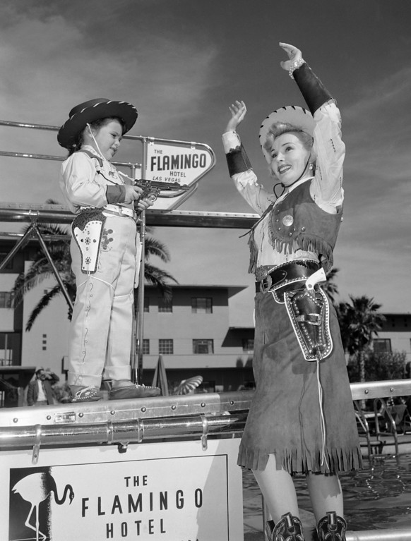 . Although generally seen in low cut evening gowns, Zsa Zsa Gabor heeded the wishes of her daughter Francesca Hilton, and went completely western between shows at a hotel in famous resort of Las Vegas, Nevada on April 4, 1953.   Francesca, age 5, has the drop on mom. (AP Photo)