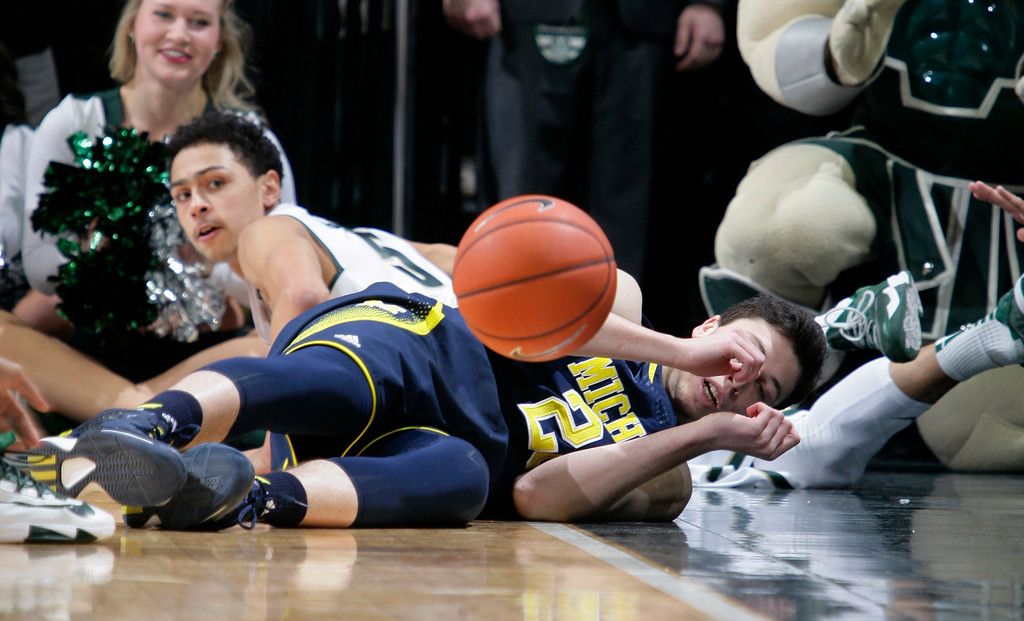 . Michigan\'s Sean Lonergan, right, and Michigan State\'s Bryn Forbes (5) dive for a loose ball during the first half of an NCAA college basketball game, Sunday, Feb. 1, 2015, in East Lansing, Mich. (AP Photo/Al Goldis)