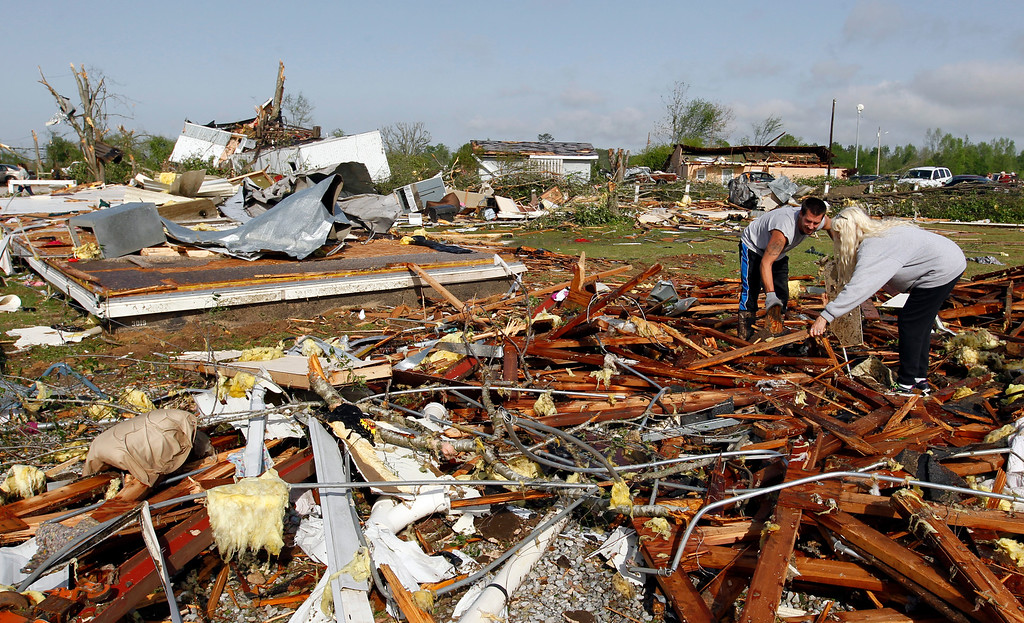 . Kevin Toon, left, and Barb Smiley, right, begin cleaning up after a tornado passed through destroying the Billy Barbs mobile home park where they lived on Tuesday, April 29, 2014, in Athens, Ala.  (AP Photo/Butch Dill)