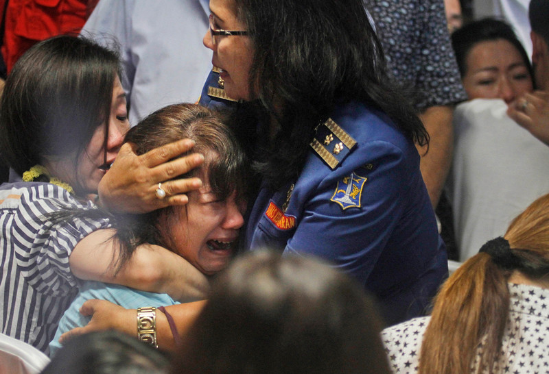 . Relatives of passengers of the missing AirAsia Flight 8501 react upon seeing the news on television about the findings of bodies on the waters near the site where the jetliner disappeared, at the crisis center at Juanda International Airport in Surabaya, East Java, Indonesia, Tuesday, Dec. 30, 2014. Bodies and debris seen floating in Indonesian waters Tuesday, painfully ended the mystery of AirAsia Flight 8501, which crashed into the Java Sea and was lost to searchers for more than two days. (AP Photo/Trisnadi)