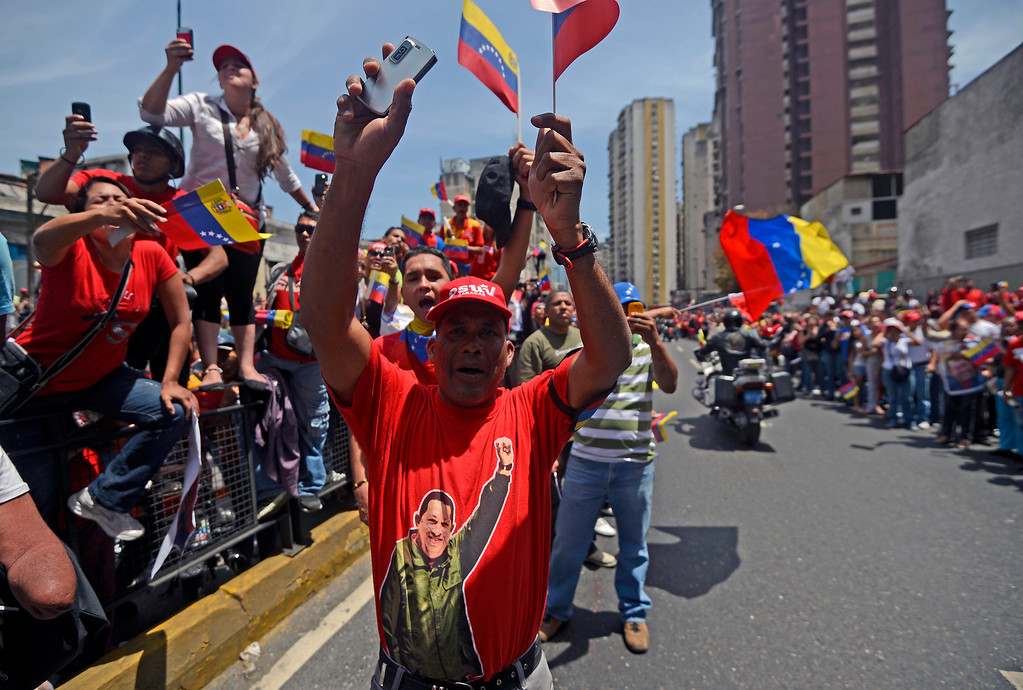 . Supporters of the late Venezuelan President Hugo Chavez wait for the passage of the funeral cortege on its way to the Military Academy, on March 6, 2013, in Caracas.   AFP PHOTO/JUAN  BARRETO/AFP/Getty Images