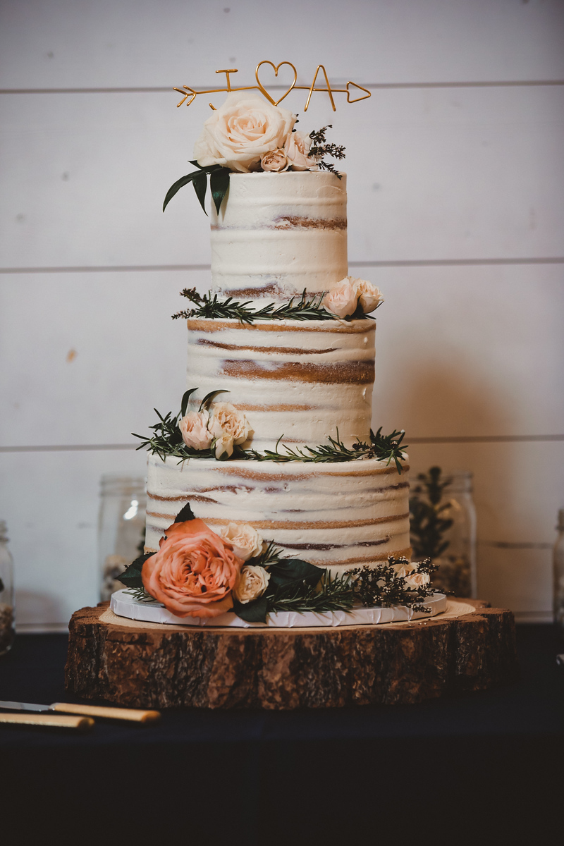 a buttercream wedding cake with greenery and flowers as decoration topped with a charming gold wire reading J hearts A with an arrow through it