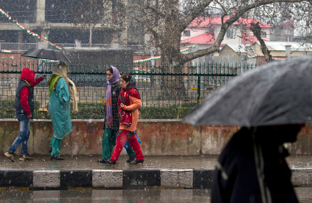. Kashmiri women walk as snow falls in Srinagar, India, Saturday, Jan. 12, 2013. Traffic on the 300 kilometers (188 miles) long Jammu-Srinagar national highway was suspended due to heavy snowfall, according to news reports. (AP Photo/ Dar Yasin)