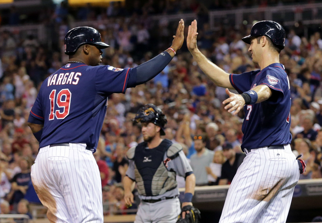 . Minnesota Twins first baseman Kennys Vargas, left, and Joe Mauer, celebrate after Mauer scored on a fielder\'s choice and Vargas scored on a wild throw from third baseman Nick Castellanos to catcher Bryan Holaday, lower center, in the sixth inning of a baseball game, Friday, Aug. 22, 2014, in Minneapolis. (AP Photo/Jim Mone)
