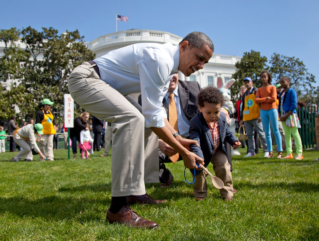 . President Barack Obama helps a little boy roll his egg to the finish line during the annual White House Easter Egg Roll, Monday, April 9, 2012, on the South Lawn of the White House in Washington.  In the background, at left are Malia Obama and Sasha Obama. (AP Photo/Carolyn Kaster)