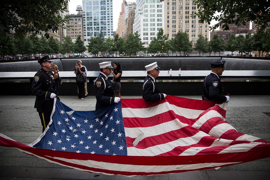 . Members of the New York Police Department, Fire Department of New York and Port Authority of New York and New Jersey Police Department carry an American flag at the beginning of the memorial observances on the 13th anniversary of the Sept. 11 terror attacks on the World Trade Center in New York, Thursday, Sept. 11, 2014.(AP Photo/Andrew Burton, Pool)