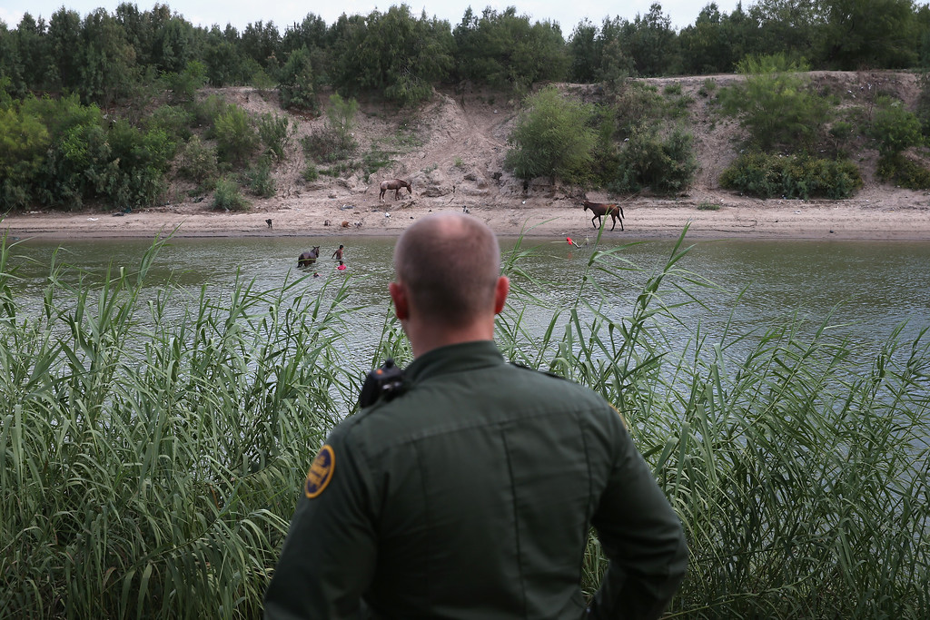 . A U.S. Border Patrol agent looks towards Mexico from the bank of the Rio Grande River on September 8, 2014 near McAllen, Texas.  (Photo by John Moore/Getty Images)