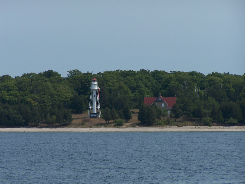 The original Plum Island Lighthouse was built in 1848 but was moved to Pilot Island some years later. The Plum Island range lights were constructed in 1896 and first lit the following year. The lights are located on the southern end of the island, the Front Light to the east, the Rear Range Light about a third of a mile to the west. These lights guide sailors safely from Lake Michigan through this sometimes difficult passage into Green Bay. The Rear Range Light consists of a tubular and skeletal shaped tower sixty-five feet tall. A spacious two-story keeper's dwelling and a fog signal building stand nearby.' The present Front Range Light is a modern metal skeletal forty-foot tower built in the 1960s.
