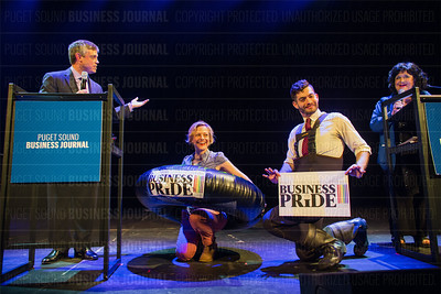 Members of the Business of Pride Ensemble entertain the audience as Emory Thomas (left), publisher of the Puget Sound Business Journal, and Patti Payne, PSBJ columnist, look on during the PSBJ's The Business Of Pride at the Paramount Theatre in Seattle on Thursday, May 26, 2016. (BUSINESS JOURNAL PHOTO | Dan DeLong)