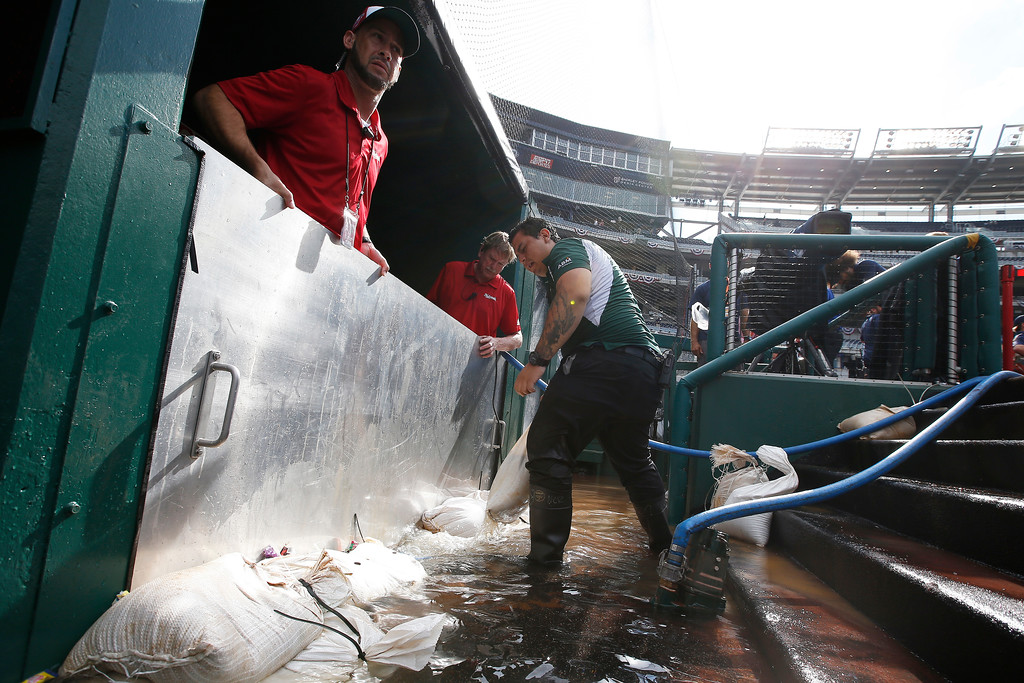 . Grounds crews clean up the water in the dugout after a thunderstorm ahead of the 89th MLB baseball All-Star Game, Tuesday, July 17, 2018, at Nationals Park, in Washington. (AP Photo/Alex Brandon)