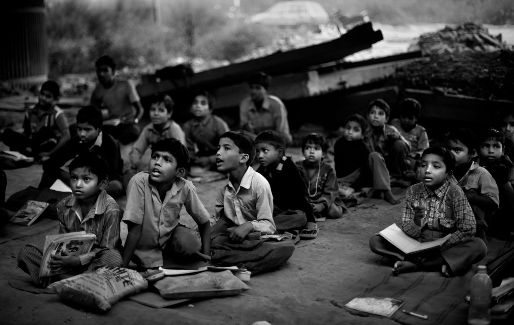 . In this Nov. 6, 2012 photo, underprivileged Indian children attend a free school run under a metro bridge in New Delhi, India. This photo was one in a series of images by Associated Press photographer Altaf Qadri that received an honorable mention in the World Press Photo 2013 photo contest for the Contemporary Issues series category. (AP Photo/Altaf Qadri, File)