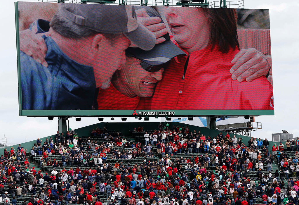 . A cene from the Boston Marathon bombings is displayed on the outfield screen before a baseball game between the Boston Red Sox and the Kansas City Royals in Boston, Saturday, April 20, 2013. (AP Photo/Michael Dwyer)