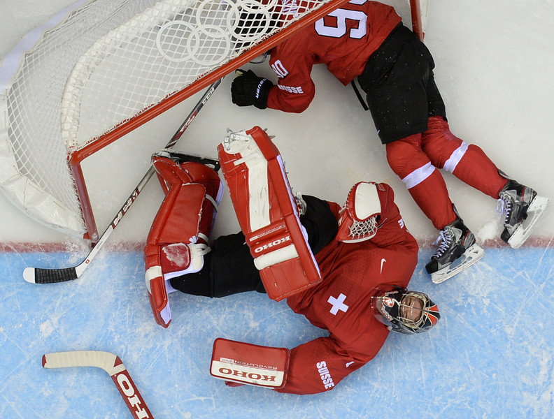 . Switzerland\'s Roman Josi and Switzerland\'s goalkeeper Jonas Hiller slide in the nets during the Men\'s Ice Hockey Play-offs Switzerland vs Latvia at the Bolshoy Ice Dome during the Sochi Winter Olympics on February 18, 2014.  (ALEXANDER NEMENOV/AFP/Getty Images)
